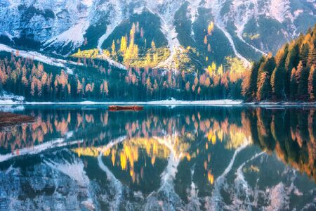 Braies lake with beautiful reflection in water at sunrise in autumn in Dolomites, Italy. Landscape with fall forest, mountains, lake, water, boats, trees with colorful foliage. Dolomiti. Italian alps