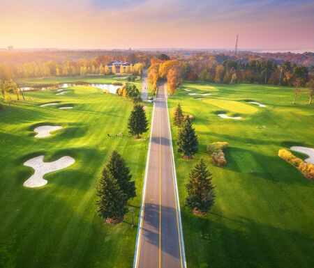 Road through the golf course at sunset in autumn. Aerial view of roadway and green golf field in fall. Landscape with route, meadow, green pine trees, orange forest, beautiful sky. View from above