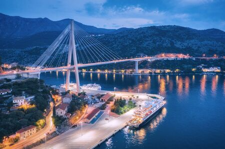 Aerial view of cruise ship in port and beautiful bridge at night. Landscape with ships and boats in harbour, city lights, road, mountains, blue sea at sunset. Top view. Floating liner at harbor