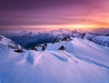Colorful red sky with clouds and bright sunlight over the snow covered mountains at sunset in winter. Beautiful wintry landscape with snowy rocks and hills at dusk. Scenery with alps at frosty evening