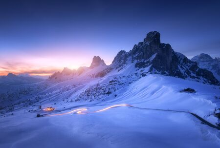Snowy mountains and blurred car headlights on the winding road at night in winter. Beautiful landscape with snow covered rocks, house, mountain roadway, blue starry sky at sunset in Dolomites, Italy