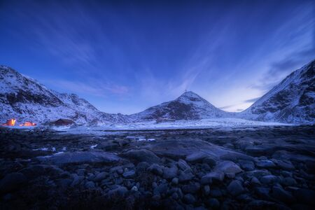 Blue sky with stars and clouds over rocky beach and snow covered mountains at night Lofoten islands, Norway. Beautiful winter landscape with stones, snowy rocks, buildings at dusk. Beautiful Nature