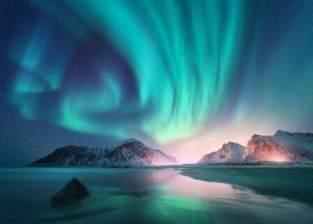 Aurora borealis over the sea, snowy mountains and city lights at night. Northern lights in Lofoten islands, Norway. Starry sky with polar lights. Winter landscape with aurora, reflection, sandy beach