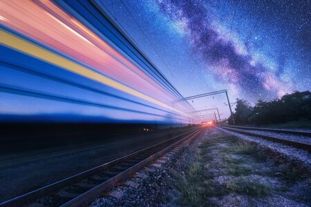 High speed train in motion and Milky Way at starry night. Industrial landscape with sky and stars over blurred modern passenger train and railroad. Railway station and space. Technology and nature