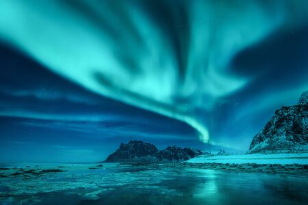 Aurora borealis over the snowy mountains and sandy beach in winter. Northern lights in Lofoten islands, Norway. Starry sky with polar lights. Night landscape with aurora, frozen sea coast, blue sky 免版税图像