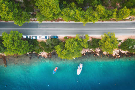 Aerial view of road in beautiful green forest and boats and yacht in the sea at sunset in summer. Colorful landscape with roadway, blue water, trees. Top view from drone of highway in Croatia. Travel