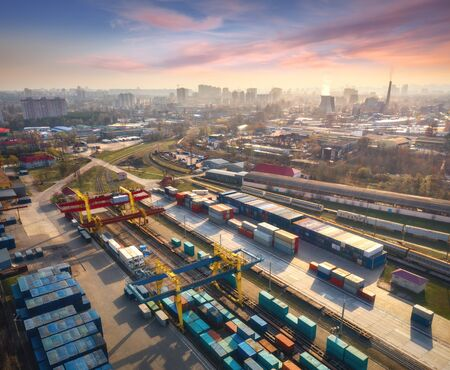 Aerial view of container loading and unloading at sunset. Top view of containers at logistics terminal in city, factory, train, railroad, sky. Business. Freight transportation containers on railway