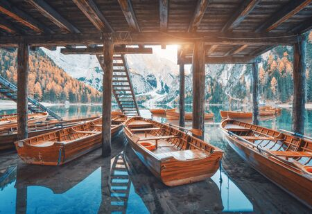 Wooden boats under the house in famous Braies lake at sunrise in autumn in Dolomites, Italy. Landscape with stairs, mountains, blue water, colorful trees in fall in dawn. Travel in Europe. Alps Фото со стока