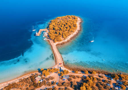 Aerial view of beutiful small island in sea bay at sunset in autumn in Murter, Croatia. Top view of clear blue water, orange trees, mountain, sandy beach, boats and yachts in fall. Tropical landscape