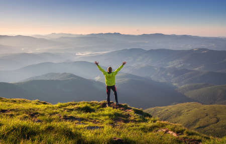 Sporty man standing on the mountain peak with raised up arms against mountain valley in fog at sunset in autumn. Happy young man, rocks, forest and blue sky in fall. Traveler hiking in mountains
