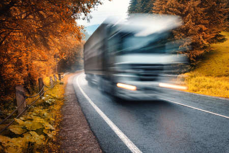 Blurred truck on the road in autumn foggy forest in rainy day. Beautiful mountain roadway, trees, orange foliage in fog. Landscape with car in motion, road through woodland in fall. Travel. Road trip 免版税图像