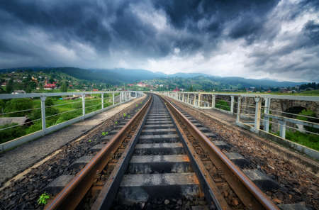 Railroad bridge in mountains in overcast day in summer. Railway station in village at moody sunset. Industrial landscape with railway platform, green trees and grass, dramatic cloudy sky, buildings