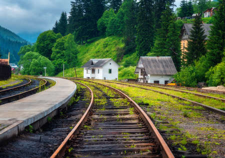 Railway station and small white house in mountain village at sunset. Rural railroad in overcast day in summer. Industrial landscape with railway platform, green trees, grass, buildings in cloudy day