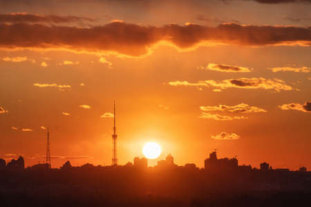 Silhouette of a Kiev city at beautiful sunset. Aerial view of buildings against colorful orange sky with sun and red clouds. Urban landscape. Background of downtown. City skyline. Cityscape 免版税图像
