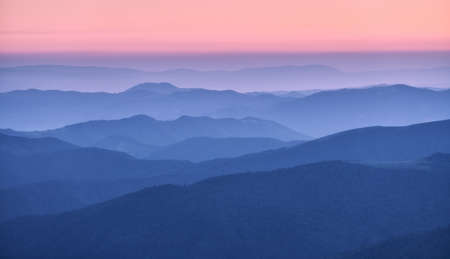 Mountain ridges in fog at sunset in autumn. Beautiful landscape with foggy mountain valley, rocks, forest, pink sky in fall at dusk in blue hour. Aerial view of hills. Top view. Nature background 免版税图像