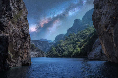 Milky Way over the beautiful mountain canyon and blue sea at night in summer. Colorful landscape with bright starry sky with Milky Way, rocks, trees, moonlight, constellation. Galaxy. Nature and space