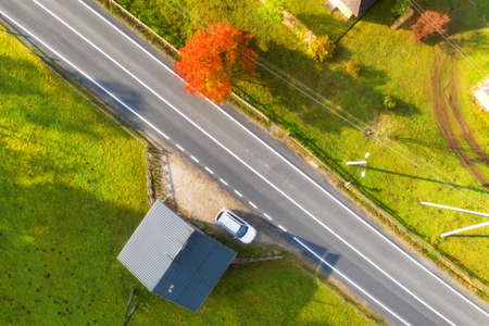 Aerial view of beautiful road in green hills at sunset in autumn. Colorful landscape with rural road, red tree, grass, car and building in fall. Top view from drone of roadway. Travel