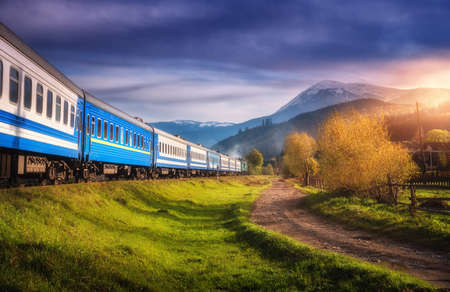 Moving train in mountains at sunset in autumn. Industrial landscape with passenger speed train on railroad, dirt road, snowy rocks, orange trees, green grass, purple sky in fall. Rural railway station