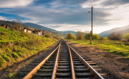 Railroad in mountains at sunset in autumn. Beautiful industrial landscape with railway station, orange trees, green grass, buildings, rocks and blue sky with clouds in fall. Rural railway platform