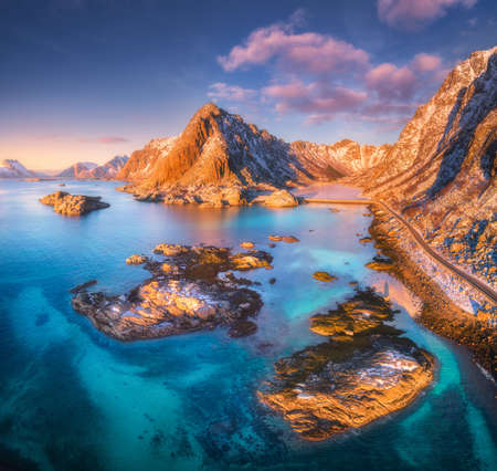 Aerial view of beautiful mountains, small islands in the sea, road, blue sky at sunset in Lofoten islands, Norway in winter. Top view of road, snowy rocks, stones, sea coast, clear water. Top view