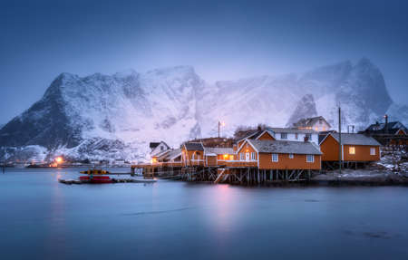 Rorbu on sea coast and snow covered mountain in fog at dusk. Lofoten islands, Norway. Moody winter landscape with traditional norwegian rorbuer, water, snowy rocks at night. Old fishermens houses