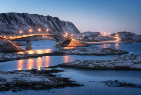 Bridge with illumination, snow covered mountains, village and blue sky with reflection in water. Night landscape with bridge, snowy rocks, city lights, sea. Winter in Lofoten islands, Norway. Road 免版税图像
