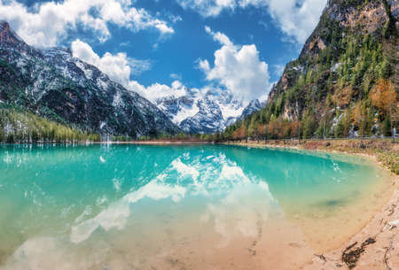 Mountain lake with reflection at sunset in autumn in Dolomites, Italy. Beautiful landscape with azure water, trees, snowy mountains, blue sky with clouds in fall. Snow covered rocks. Nature 免版税图像