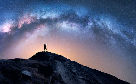 Arched Milky Way and happy man on the mountain at night. Silhouette of guy with raised up arm on the hill, sky with stars, yellow light in Nepal. Galaxy. Space landscape with milky way arch. Travel