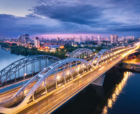 Aerial view of beautiful bridge at night in Kiev, Ukraine. Landscape with bridge, river, city illumination, blue sky with clouds at sunset. Cityscape with road, cars, buildings, city lights. Top view