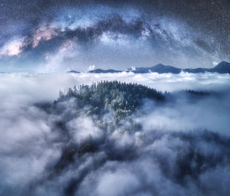 Milky Way arch over the mountains in low clouds at starry night in summer. Landscape with sky with stars, arched Milky Way, trees on the hill in fog, mountain peaks. Space and galaxy. Aerial view 免版税图像
