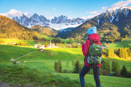 Beautiful young woman with backpack is standing on the hill in mountains at sunset in autumn. Landscape with sporty girl, rocks with snowy peaks, green meadow, orange trees, blue sky in Italy. Travel
