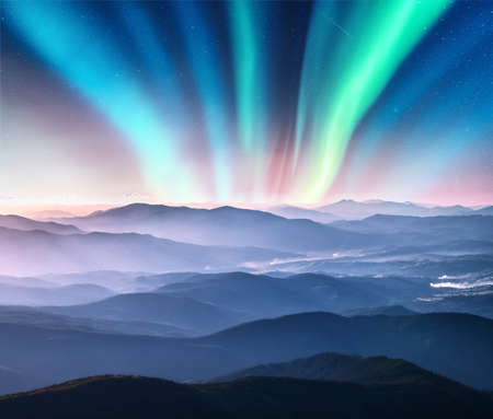 Aurora borealis above the mountain valley in low clouds at night. Northern lights in winter. Night landscape with polar lights, mountains in fog, sunlight, starry sky. Aurora over the foggy hills