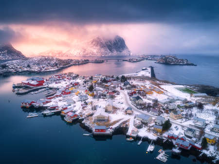 Aerial view of snowy mountain, village on sea coast, cloudy orange sky at sunset in winter. Top view of Reine, Lofoten islands, Norway. Moody landscape with high rocks, rorbu, reflection in water 免版税图像
