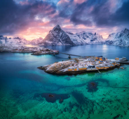 Aerial view of Hamnoy at sunset in winter in Lofoten islands, Norway. Moody landscape with blue sea, snowy mountains, rocks, village, buildings, rorbuer, road, bridge, colorful cloudy sky. Top view 免版税图像