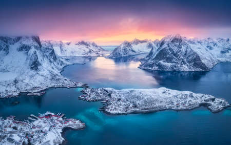 Aerial view of Reine at sunset in winter. Top view of Lofoten islands, Norway. Landscape with blue sea, snowy mountains, high rocks, village with buildings, rorbu, colorful sky, reflection in water