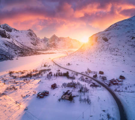 Beautiful road in snowy mountains in winter at sunset. Aerial view. Lofoten Islands, Norway. Colorful landscape with roadway, rocks in snow, houses and sky with sunlight and pink clouds. Top view
