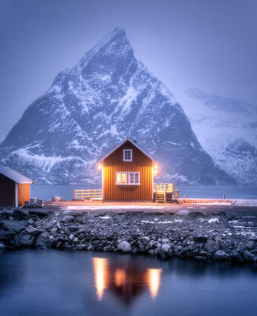 Alone rorbu on sea coast and snow covered mountain at night in winter. Lofoten islands, Norway. Landscape with traditional norwegian rorbuer, reflection in water, snowy rocks, fog. Old fishermen house