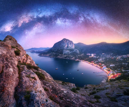 Arched Milky Way over the beautiful mountains and sea coast at night in summer. Colorful landscape with rock, bright starry sky, Milky Way arch, city lights, boats and yachts. Galaxy. Nature and space 免版税图像