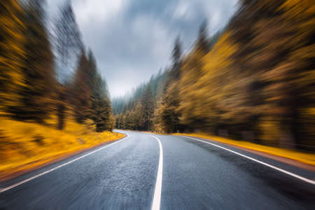 Road in autumn foggy forest in rainy day with motion blur effect. Beautiful mountain roadway and blurred background with orange trees in fog. Empty asphalt road through woodland in speed motion. Fall