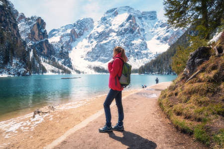 Young woman with backpack on the snowy shore of Braies lake with clear water at sunny bright day in winter. Travel. Landscape with slim girl, reflection in water, mountains, green trees, blue sky 免版税图像