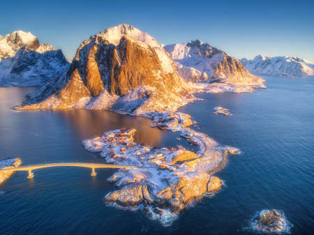 Aerial view of Hamnoy at sunrise in winter. Lofoten islands, Norway. Panoramic colorful landscape with blue sea, snowy mountains, islands, rocks, village, rorbu, road, bridge, sky. Top view from drone