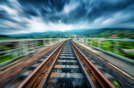 Railroad bridge in mountains in overcast day with motion blur effect. Railway station and blurred background at moody sunset. Industrial landscape with railway platform in speed motion. Concept