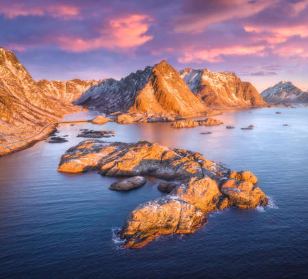 Aerial view of rocks in the sea, snowy mountains, blue sky with clouds at sunset. Travel in Lofoten Islands, Norway. Winter landscape with small islands in water, cliffs and waves. View from above