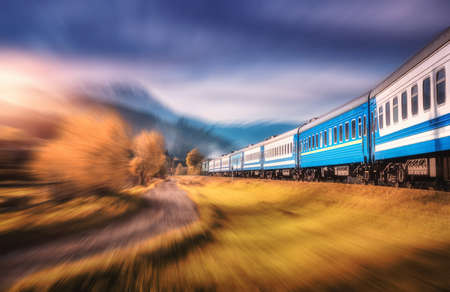 Moving train in mountains at sunset in autumn with motion blur effect. Industrial landscape with passenger speed train on railroad and blurred background with orange trees, grass. Railway station