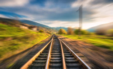 Railroad in mountains with motion blur effect at sunset in autumn. Industrial landscape with railway station and blurred background with sky, trees, grass. Railway platform in speed motion, Concept