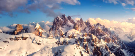 Snowy mountains in low clouds and blue sky at sunset in winter. Panoramic landscape with beautiful snow covered rocks in fog in frosty evening. Aerial view of high peaks. Alps in Dolomites, Italy