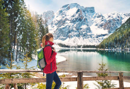 Young woman with backpack near wooden fence and snowy shore of Braies lake with clear water at sunny day in winter. Travel. Landscape with slim girl, reflection in water, mountains in snow, trees