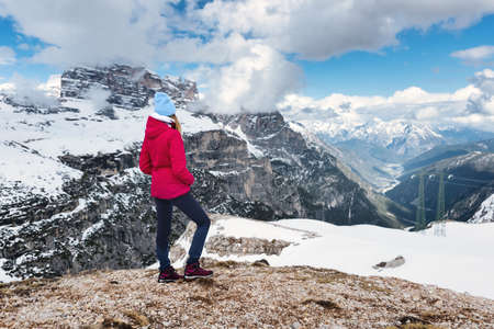 Young woman in red jacket on the hill against snowy mountains at sunset in winter. Landscape with sporty girl, rocks in snow, trail, blue sky with clouds. Travel in Dolomites, Italy. Tourism 免版税图像