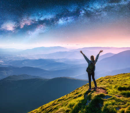 Happy young woman on the mountain peak and arched Milky Way over mountains at night. Landscape with girl, blue starry sky, Milky Way Arch, green grass, hills in fog. Space and galaxy. Sky with stars 免版税图像