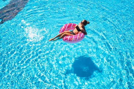 Beautiful young woman swimming on the pink donut swim ring in transparent blue water at sunset in summer. Tropical landscape with sexy slim girl in pool, clear water. Top view. Travel. Aerial view 免版税图像